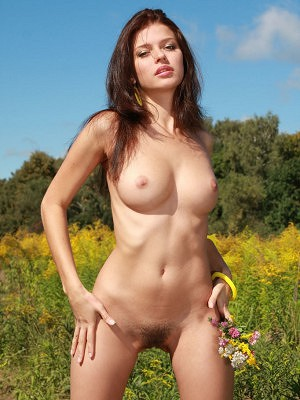 """""""Liza J flaunts her delectable unshaven labia with a warm, engaging smile outdoors."""""""