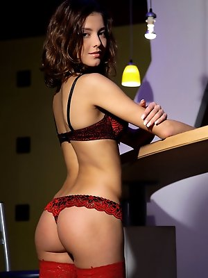 A seductive Divina A poses in her deep crimson matching lingerie and matching red fishnet stockings that amplifies her sultry, irresistible appeal.